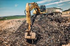 Grävskopa som arbetar på stads- avfall som dumpar jordning arkivbild