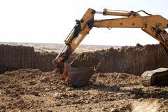 Grävskopa som arbetar på utgrävningen Arkivfoto