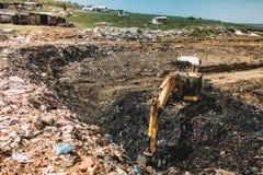 grävskopa som gör byggnationer på avskrädedumpsite Arkivfoto
