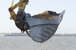 Grävskopa som muddrar en hamn Arkivfoto