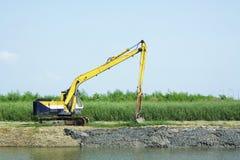 Grävskopa som muddrar kanalen Arkivbild