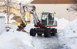 Grävskopa som tar bort snö Royaltyfria Bilder