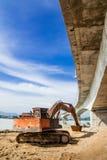 Grävskopa under en bro Arkivbild