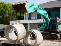 Grävskopaflyttning ett konkret rör i konstruktionsplats royaltyfri foto