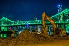 Grävskopamaskin på kust av den glödande staden fotografering för bildbyråer