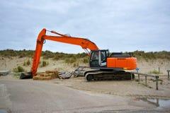 Grävskopamedel för byggande upp sand på stranden på Paal 9 efter en tung storm på Texel royaltyfri bild