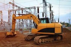 Grävskopanärbild av stekflottskopan av jord på konstruktionsplats av den elektriska stationen med industriella equipmen Fotografering för Bildbyråer