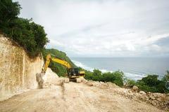 Grävskopan fungerar på en vaggaklippa som stenlägger vägen till havet Landskap med skogen och havet Arkivfoton