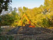 Grävskopan gräver jorden Arkivfoton