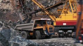 Grävskopan laddar en sten i den tunga lastbilen i villebrådet som bryter granit arkivfilmer