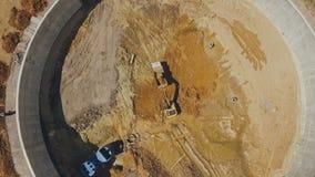 Grävskopan laddar jordning in i lastbilen på konstruktion av trafikutbyte, antennskott stock video