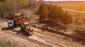 Grävskopan laddar sanden in i lastbilen Arbetare gör vägen royaltyfria foton