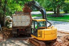 Grävskopan laddar smuts på lastbilen för konstruktion Arkivfoton