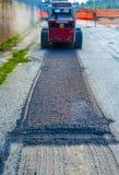 Grävskopan utför malning av asfalt Arkivbild