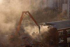 Grävskoparivning i solbelyst dammmoln demonterar buildinen Arkivfoto
