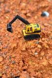GrävskopaToy arbete på konstruktionsplatsen Arkivfoton