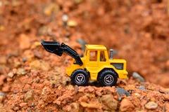 GrävskopaToy arbete på konstruktionsplatsen Arkivfoto