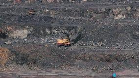 Grävskopor och tunga lastbilar i villebrådet som bryter granit arkivfilmer