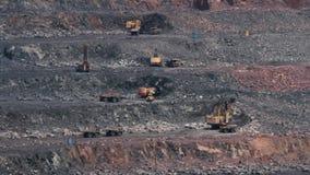 Grävskopor och tunga lastbilar i villebrådet som bryter granit stock video