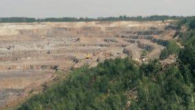 Grävskopor och tunga lastbilar i villebrådet som bryter granit TILT-SHIFT arkivfilmer