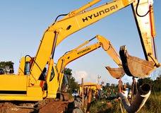 Grävskopor som rymmer rörledningen på träsk royaltyfri fotografi