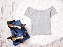 Grå överkant, jeans och svarta skor på vit päls, trendigt begrepp Fotografering för Bildbyråer