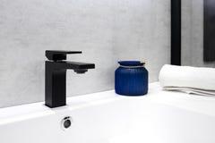 Grå badruminre med den glass kruset för vita för vasksvart moderna för techno för stil blått för vattenkran och vithandduken Royaltyfri Fotografi