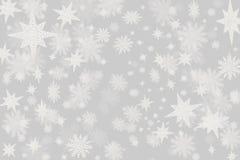 Grå bakgrund för jul med lotter av snöflingor och stjärnor w royaltyfri foto