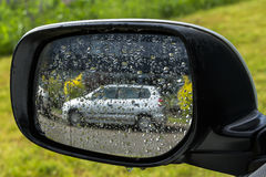 Grå bilreflexion i en våt mirro för bakre sikt Royaltyfri Foto