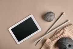 Grå boll för handarbetegarn, stickor och en minnestavla med en svart skärm, bästa sikt Royaltyfri Bild