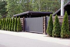 Grå brun port och ett staket med dekorativa träd som är främsta av en asfaltväg fotografering för bildbyråer