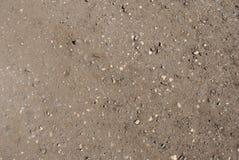 Grå brun sand med färgstänk av ljusa kiselstenar arkivfoton