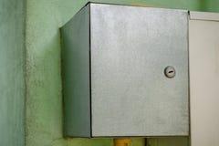 Grå elkraft- eller gasströmbrytareask som hänger på väggen utrustning Royaltyfri Bild