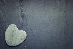 Grå en formad zenhjärta vaggar i hörnet på en tegelplattabakgrund Royaltyfria Bilder