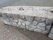Grå färgcementbarrikad med stenar och metall royaltyfria bilder