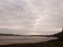 Grå färgen för skymning för lågvattensommarhimmel fördunklar lynne och reds med riv Arkivfoto