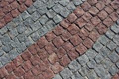 Grå färger och en röd tegelplatta på en trottoardiagonal Royaltyfria Foton