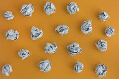 Grå färger skrynklade pappers- bollar på en gul bakgrund Arkivbilder
