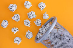 Grå färger skrynklade pappers- bollar som rullar ut ur en soptunna Royaltyfria Foton