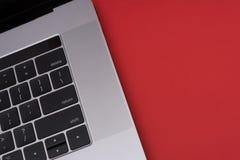 Grå färgmetallbärbar dator på den röda bakgrunden Slapp fokus royaltyfria foton