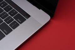 Grå färgmetallbärbar dator på den röda bakgrunden Slapp fokus royaltyfri foto