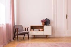 Grå färgtappningfåtölj bredvid träkabinettet med böcker och ljung i krukan, verkligt foto med kopieringsutrymme på den tomma vägg arkivfoto