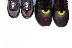 Grå färgungegymnastikskor med små röda hjärta och par av svarta vuxna gymnastikskor royaltyfri bild
