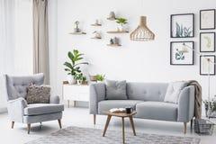 Grå fåtölj bredvid soffa i ljus vardagsruminre med affischer och trätabellen Verkligt foto royaltyfri fotografi