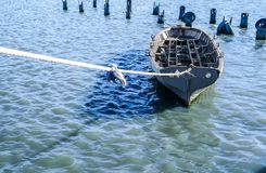 Grå fiskebåt som binds med ett rep i blått-gräsplan vatten royaltyfri fotografi