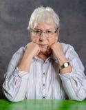 Grå hårig äldre kvinna med exponeringsglas som ser allvarliga Arkivfoton