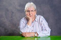 Grå hårig äldre kvinna med exponeringsglas som ser allvarliga Arkivbilder