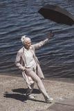 Grå haired kvinna som går med paraplyet på flodkust på dagen Royaltyfria Bilder