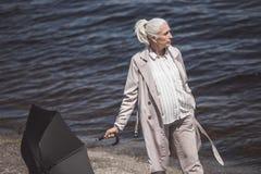 Grå haired kvinna som går med paraplyet på flodkust på dagen Fotografering för Bildbyråer