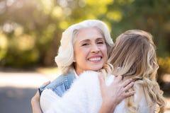 Grå haired kvinna som kramar hennes dotter Royaltyfria Bilder